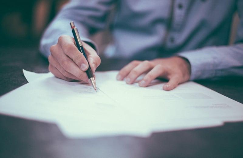 homme qui signe sur un papier